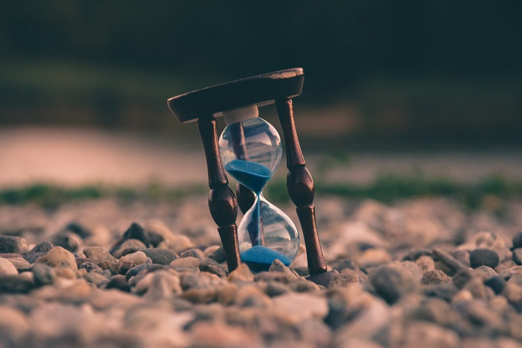 An hourglass rests in the sand with half the grains of sand remaining in the top half. There is still plenty of living to be done.