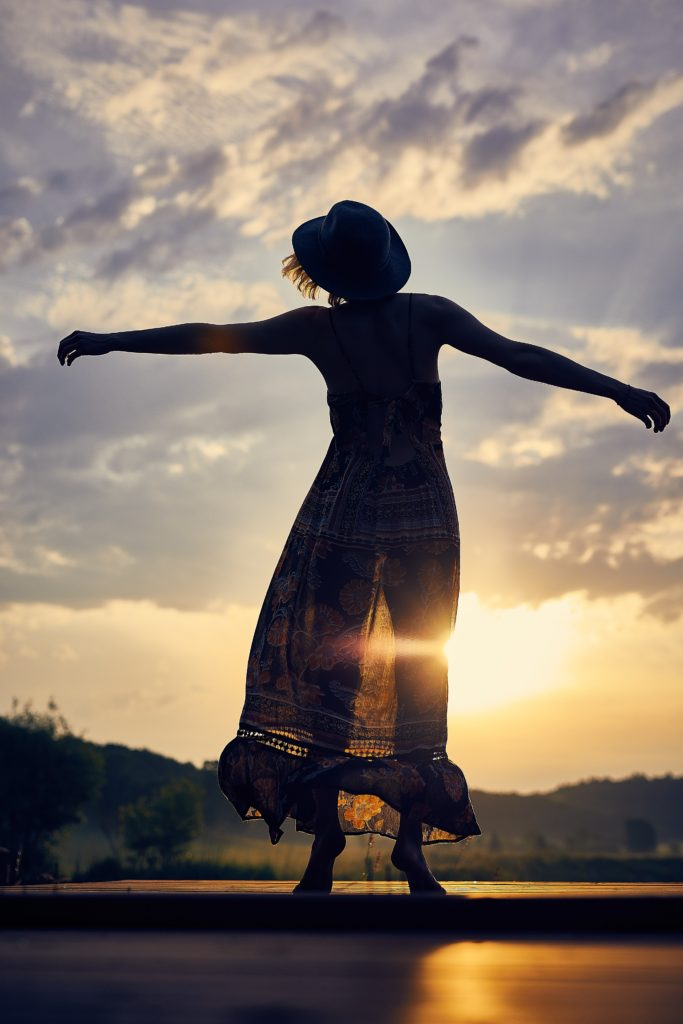 A happy woman in a summer dress stands with arms wide, heart open and head tilted back to face the sun.