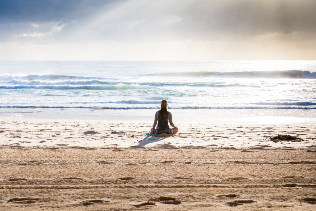 A woman enjoys the present moment, sitting on the beach and meditating as the tide rolls in.