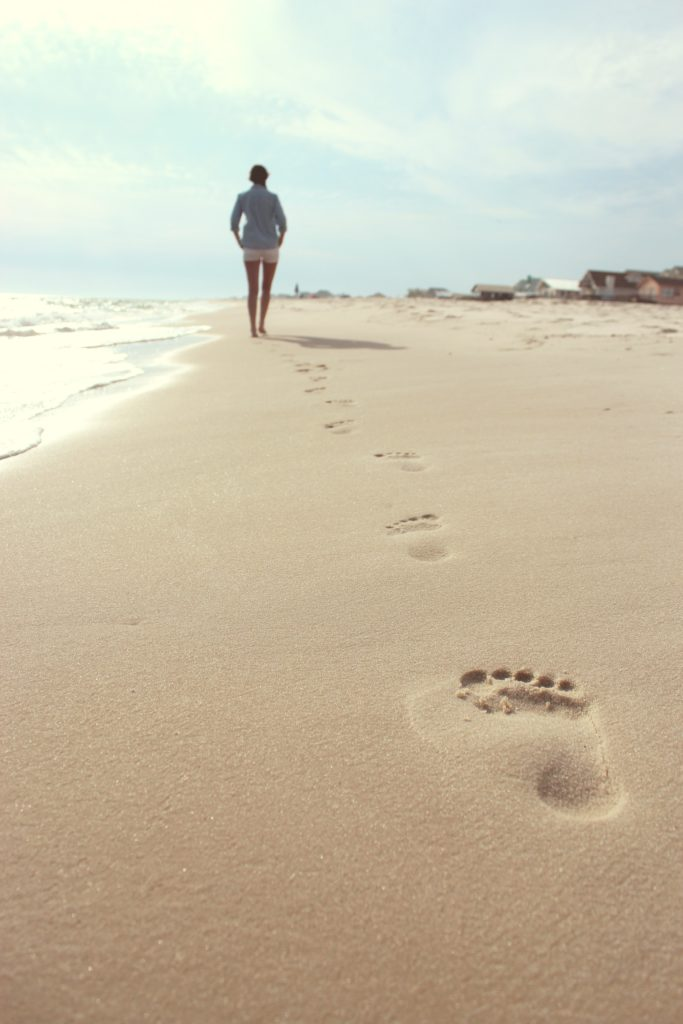 Woman walking down a beach, leaving footprints in the sand.