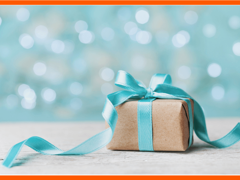 A beautifully wrapped gift sits in front of a sparkling background. Each day is gift, full of promise and possibility. Savor the gifts of the day.