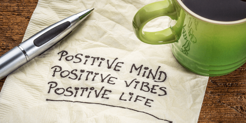 A coffee mug and pen sit on a napkin. On the napkin, the following note is written: Positive mind, positive vibe, positive life.