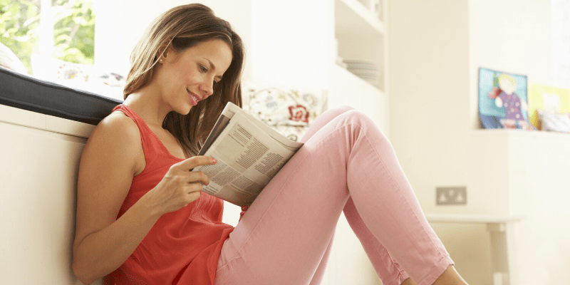 A woman reads a newspaper, smiling as she scan the page. She is seeking and finding good news.