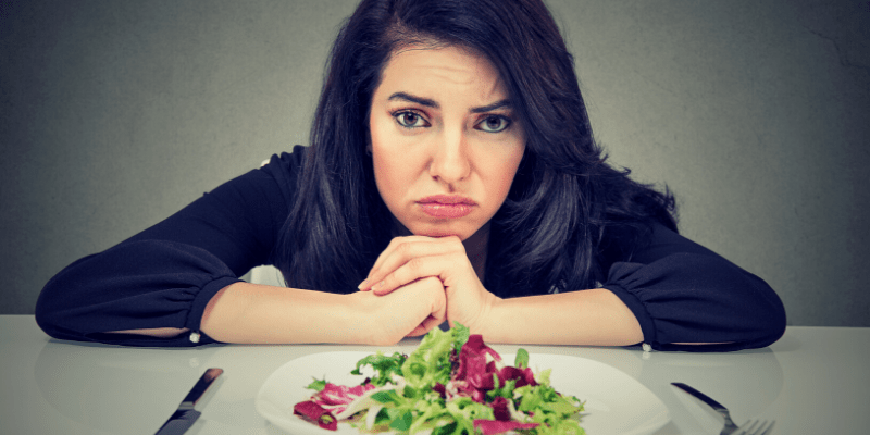 A woman stares forlornly at a simple salad. Diets are no fun.