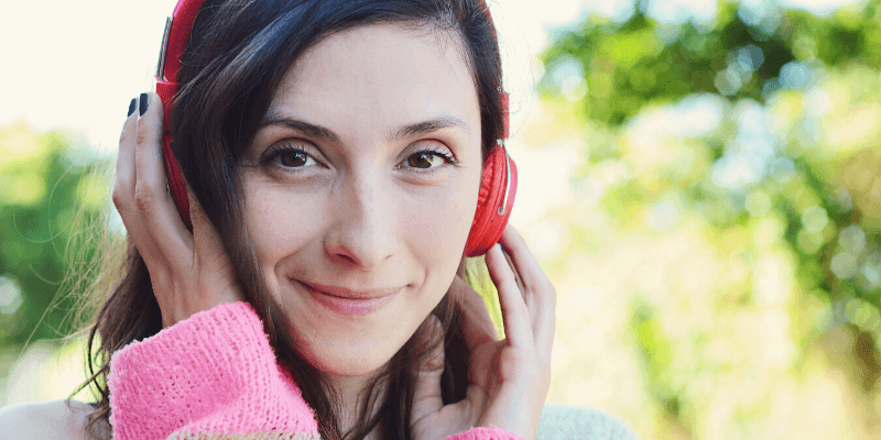 A woman smiles, holding headphones to her ears. She has turned off the noise that surrounds her.