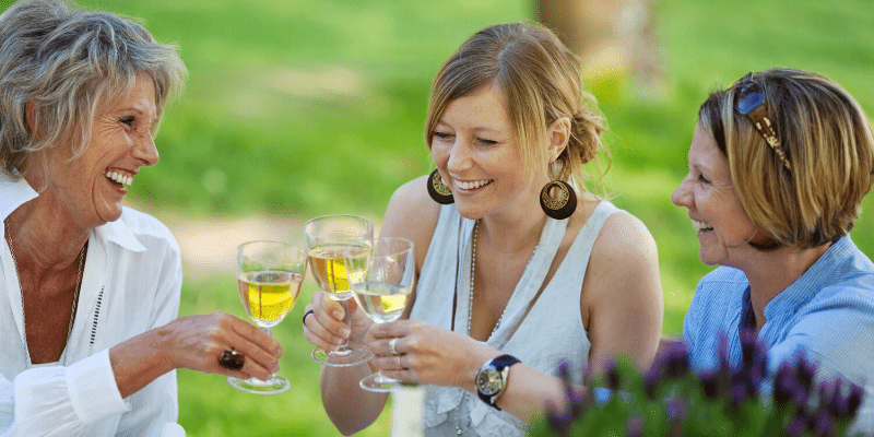 Three woman raise their wine glasses in a toast. They are laughing and focused on the positive for a happier life.