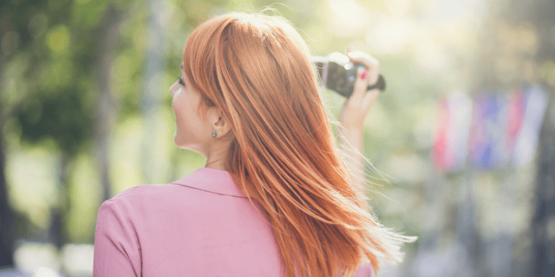A smiling woman faces into the sunlight, holding a video camera. She is focused on the positive.
