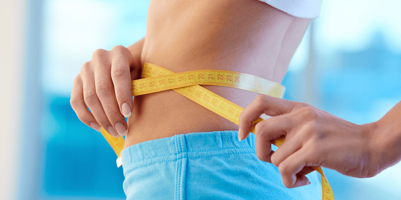 A slim woman's waist is wrapped with a tape measure, showing her dieting progress.