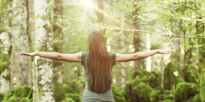 A woman stands in a forest, her arms stretched out to her sides in perfect balance.