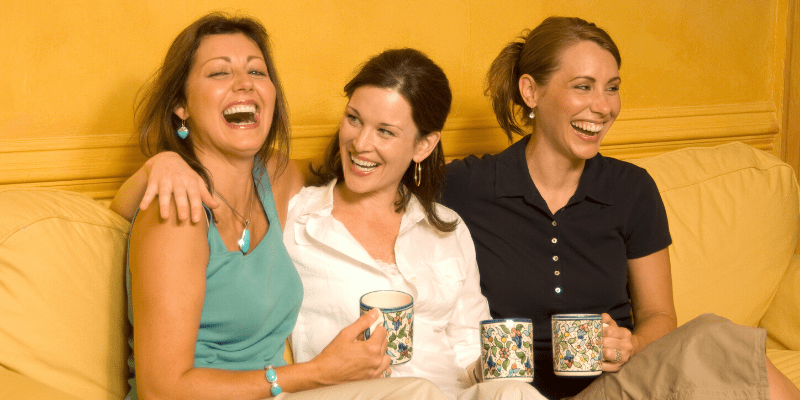 Women friends laugh over coffee
