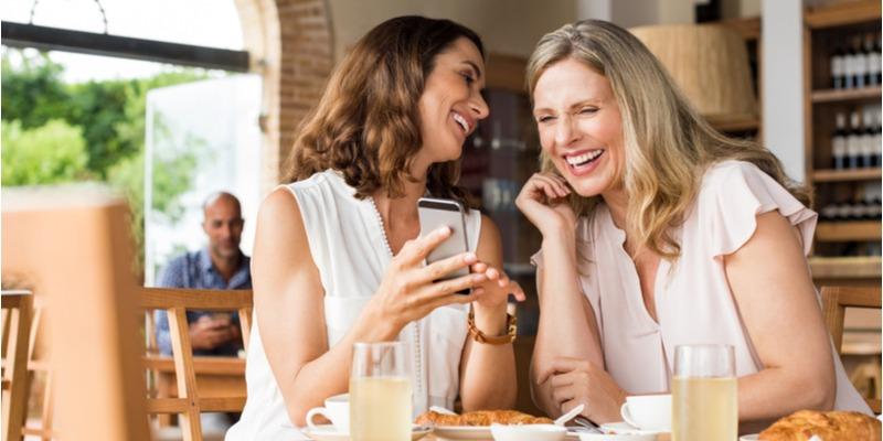 Two women laugh together as they watch a funny video on a cell phone. These are the best of times. Their positive outlook leads to happiness.