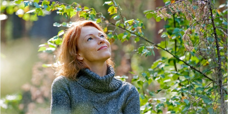 A woman walks in the woods, enjoying her solitary time in nature. She is tranquil and happy in the present moment.