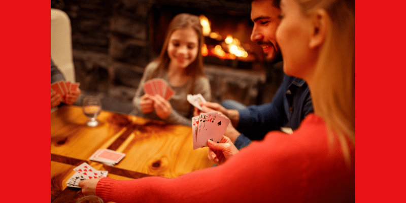 Family game night. A family plays a game of cards together, enjoying their time together at home.