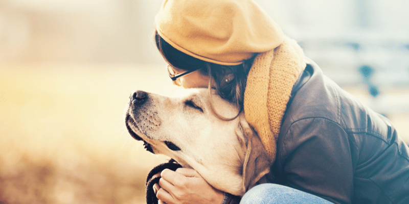 A woman hugs her dog, the dog's face is content, happy to be in it's owner's embrace.