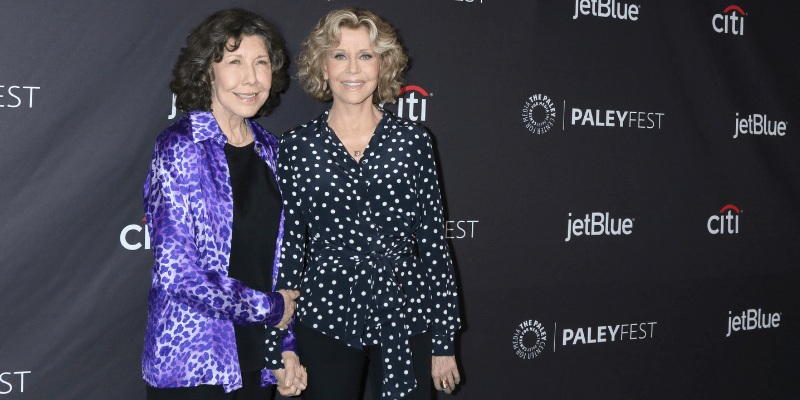 """Lily Tomlin and Jane Fonda, costars of the hit Netflix series """"grace and Frankie"""" pose together at PaleyFest event. The women smile and hold hands."""