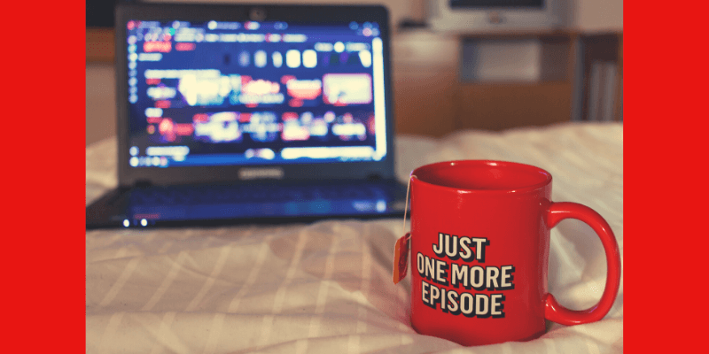 """A laptop sits open on a bed, ready to air the latest episode of Grace and Frankie. Next to it sits a mug of tea with the quote """"Just one more episode!"""""""