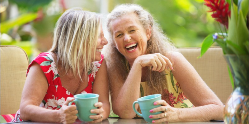 Two old friends sit together, coffee cups in hand. The women lean into each other, laughing.