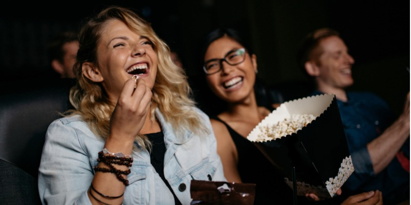 """Two women sit in a dark room, eating popcorn and laughing together as they watch a comedy like """"Grace and Frankie"""""""