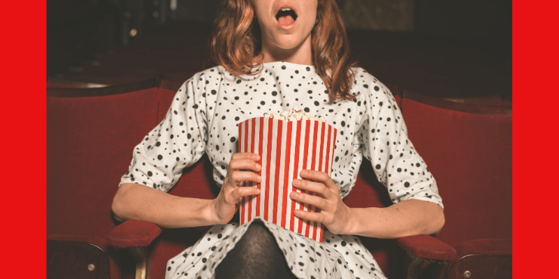A woman sits in a movie theatre, popcorn on her lap. Her mouth is open in surprise as she stares at the screen. What will happen next?