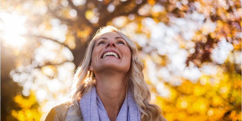 A joyful woman turns her face to the sun. Even in our darkest moments, life can still be full of fierce joy.
