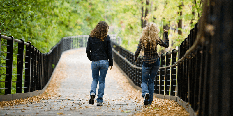 Two women walk down a wooded trail, maintaining a safe distance from each other.  The pandemic is here, but you can still get outside and connect with people and nature from a 6 foot distance.