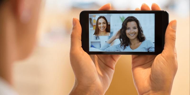 A woman stays connected with her friends using Facetime. People need face-to-face time, using cell phone features like Facetime allows us to stay connected.