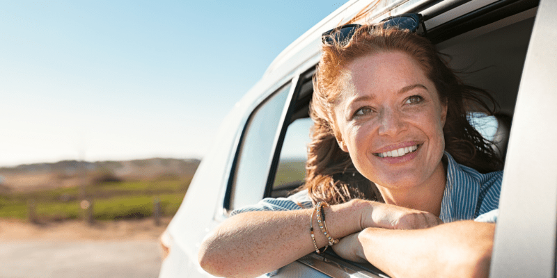 A woman leans out her car window on a sunny day, ready to greet a friend.
