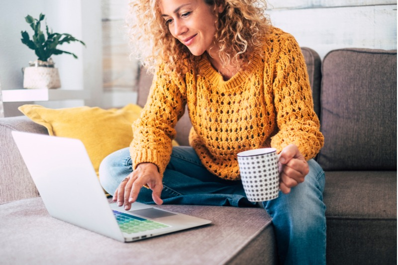 A woman sits on a sofa and looks at her laptop, a cup of coffee in her hand. It requires a creative approach to stay connected while isolated.