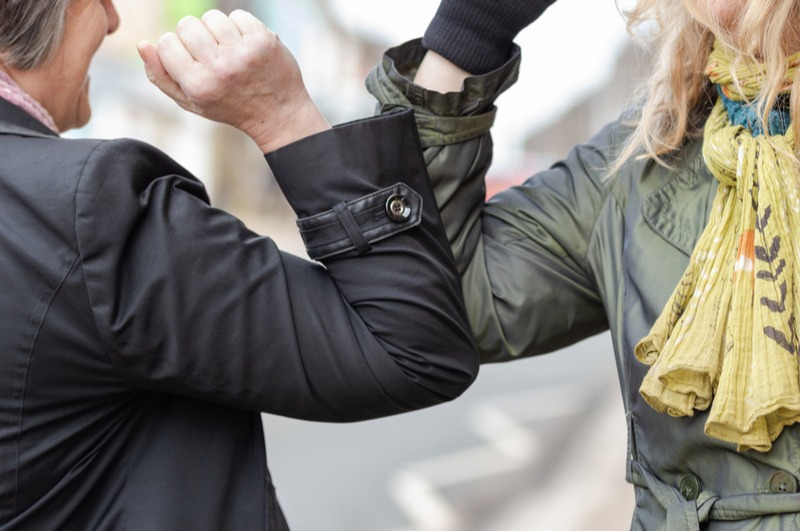 Two women bump elbows, a new greeting that has rapidly replaced handshakes and hugs thanks to the onset of COVID-19. Connect in a safe way.