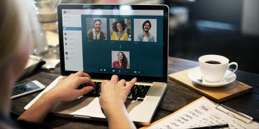 A woman types on a laptop keyboard as she participates in a virtual meeting. The video images of four friends are arranged on the screen. Technology makes virtual connecting easy.