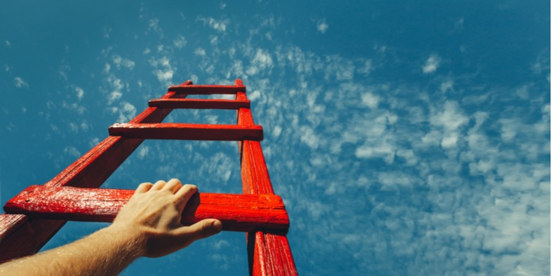 A bright red ladder extends into a bright blue sky as someone begins to climb. It's time to stop wishing and start doing.